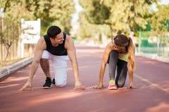 Giovani coppie pronte per una corsa Immagini Stock