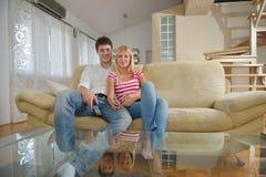 Giovani coppie rilassate che guardano TV a casa Immagine Stock Libera da Diritti