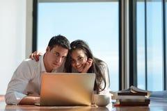 Giovani coppie rilassate che lavorano al computer portatile a casa Immagini Stock Libere da Diritti