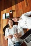 Giovani coppie rilassate che lavorano al computer portatile a casa Fotografia Stock Libera da Diritti