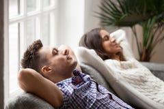 Giovani coppie rilassate che riposano insieme sullo strato comodo a casa fotografia stock