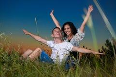 Giovani coppie romantiche a braccia aperte e divertendosi al tramonto su paesaggio all'aperto e bello e sul cielo scuro, concetto Fotografia Stock Libera da Diritti