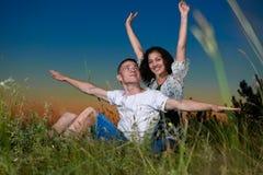 Giovani coppie romantiche a braccia aperte e divertendosi al tramonto su paesaggio all'aperto e bello e sul cielo scuro, concetto Fotografie Stock Libere da Diritti
