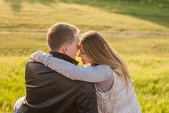 Giovani coppie romantiche che godono della natura che si siede in un abbraccio vicino, vista di autunno da dietro fotografia stock libera da diritti