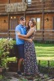 Giovani coppie romantiche che si abbracciano sui precedenti dell'hotel in uno stile rustico Immagini Stock Libere da Diritti