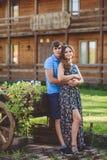 Giovani coppie romantiche che si abbracciano sui precedenti dell'hotel in uno stile rustico Fotografia Stock