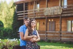Giovani coppie romantiche che si abbracciano sui precedenti dell'hotel in uno stile rustico Immagini Stock