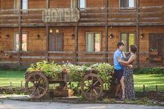 Giovani coppie romantiche che si abbracciano vicino all'carretti di legno decorativi con i fiori, su un fondo di stile rustico Fotografia Stock