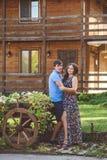 Giovani coppie romantiche che si abbracciano vicino all'carretti di legno decorativi con i fiori, su un fondo di stile rustico Fotografia Stock Libera da Diritti