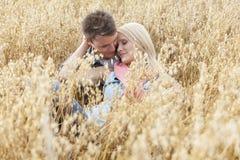 Giovani coppie romantiche che si rilassano in mezzo del campo fotografia stock