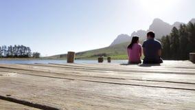 Giovani coppie romantiche che si siedono sull'estremità del molo di legno dal lago stock footage