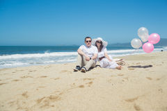 Giovani coppie romantiche che si siedono sulla spiaggia con i palloni Fotografie Stock