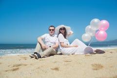 Giovani coppie romantiche che si siedono sulla spiaggia con i palloni Fotografie Stock Libere da Diritti