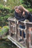 Giovani coppie romantiche che stanno sul ponte che considera il wate Immagini Stock Libere da Diritti