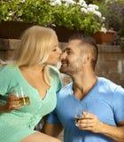 Giovani coppie romantiche con le bevande in giardino Immagini Stock