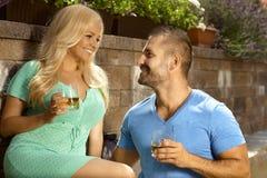 Giovani coppie romantiche con le bevande in giardino Fotografia Stock