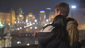 Giovani coppie romantiche nell'amore che abbraccia e che esamina paesaggio urbano stupefacente di notte video d archivio