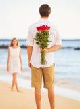 Giovani coppie romantiche nell'amore, mazzo di sorpresa della tenuta dell'uomo della r Fotografia Stock
