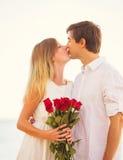 Giovani coppie romantiche nell'amore, mazzo di sorpresa della tenuta dell'uomo della r Fotografia Stock Libera da Diritti