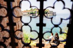 Giovani coppie romantiche nell'amore sopra la riva di mare sopra Sveti Stefan immagine stock