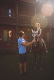 Giovani coppie romantiche nell'amore, una passeggiata su un cavallo sul fondo della natura ed hotel in stile country di legno Gio Fotografie Stock