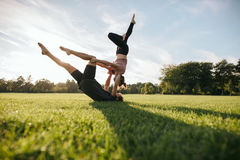 Giovani coppie sane che fanno yoga di acro su erba fotografia stock