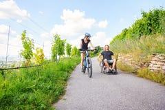 Giovani coppie in sedia a rotelle che gode del tempo all'aperto Fotografia Stock