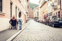 Giovani coppie in sedia a rotelle che passeggia nella città Immagini Stock Libere da Diritti