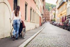 Giovani coppie in sedia a rotelle che passeggia nella città Fotografie Stock Libere da Diritti