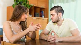Giovani coppie serie che parlano a casa immagini stock libere da diritti