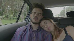 Giovani coppie sonnolente che prendono un pelo che ha il resto in un'automobile sulla strada durante la vacanza di viaggio - video d archivio