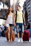 Giovani coppie sorridenti in breve che camminano attraverso la città Immagine Stock