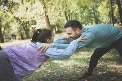 Giovani coppie sorridenti che allungano insieme prima del risolvere Fotografia Stock