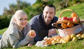 Giovani coppie sorridenti che chiacchierano come avendo picnic Fotografie Stock Libere da Diritti