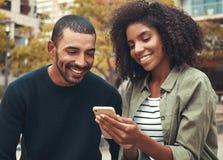 Giovani coppie sorridenti che esaminano smartphone immagini stock libere da diritti