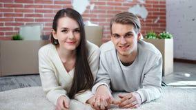 Giovani coppie sorridenti che si tengono per mano menzogne sul pavimento che posa esaminando il primo piano di medium della macch archivi video
