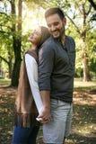 Giovani coppie sorridenti che stanno nel parco immagine stock