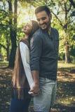 Giovani coppie sorridenti che stanno nel parco di nuovo alla parte posteriore e che tengono h fotografia stock