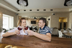 Giovani coppie sorridenti che tostano i vetri di vino al contatore del ristorante Fotografie Stock Libere da Diritti