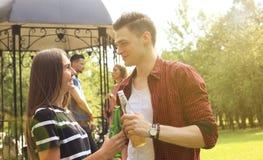 Giovani coppie sorridenti con birra ed esaminarse mentre due genti che arrostiscono col barbecue nei precedenti Fotografia Stock