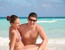 Giovani coppie sorridenti contro l'oceano fotografia stock