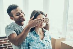 Giovani coppie sorridenti divertendosi muoversi nella nuova casa fotografia stock