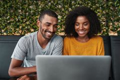 Giovani coppie sorridenti per mezzo del computer portatile fotografia stock