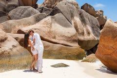 Giovani coppie sposate mettendo su spiaggia sabbiosa Fotografia Stock Libera da Diritti