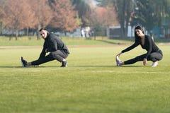 Giovani coppie Streching essi gambe prima di correre all'aperto Fotografia Stock