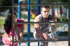 Giovani coppie Streching essi gambe prima di correre all'aperto Fotografie Stock