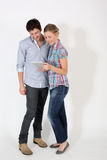 Giovani coppie su fondo bianco con la compressa Fotografie Stock Libere da Diritti