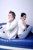 Giovani coppie sui telefoni delle cellule Immagine Stock
