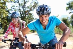 Giovani coppie sul giro della bici del paese Fotografia Stock