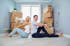 Giovani coppie sul pavimento in una nuova casa fotografia stock